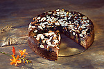 Healthy home-made Banana bread, sugar-free with almond flour, berries and almonds on a table, artistic country style food still life on rustic wooden background Image © MaximImages, License at https://www.maximimages.com