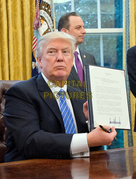 United States President Donald Trump shows the Executive Order titled &quot;Mexico City&quot; which bans federal funding of abortions overseas after signing it in the Oval Office of the White House in Washington, DC on Monday, January 23, 2017.  The other two Executive Orders concerned withdrawing the US from the Trans-Pacific Partnership (TPP)  and a US Government hiring freeze for all departments but the military,. <br /> CAP/MPI/CNP/RS<br /> &copy;RS/CNP/MPI/Capital Pictures