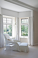 An armchair and footstool with matching loose covers in the bay window of the white bedroom