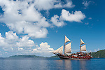 Misool, Raja Ampat, Indonesia; Wayilbatan area, a red, wooden sailing ship with it's sails raised, reflecting in the water's rippled surface