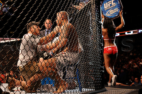 24.09.2011. Denver, Colorado. Mark Hunt is tended to by trainers as an Octagon Girl rounds the ocrtagon during UFC 135 at the Pepsi Center in Denver, Colorado.