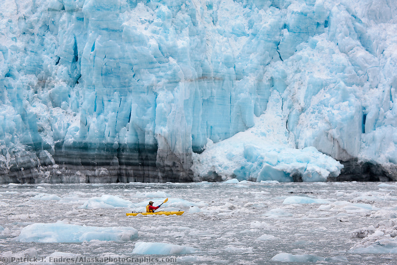 Man paddles a sea kayak through the brash ice near the face of Surprise tidewater glacier in Prince William Sound, southcentral, Alaska.