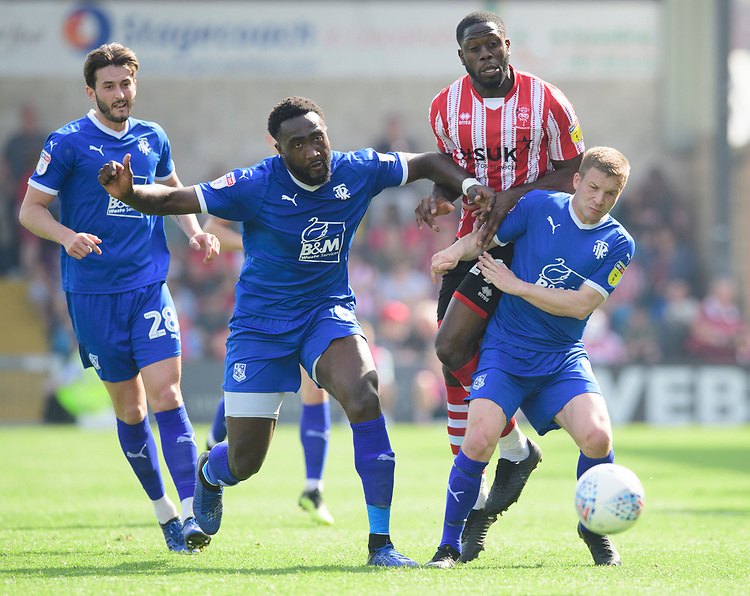 Lincoln City's John Akinde vies for possession with Tranmere Rovers' Emmanuel Monthe, left, and Tranmere Rovers' Jay Harris<br /> <br /> Photographer Chris Vaughan/CameraSport<br /> <br /> The EFL Sky Bet League Two - Lincoln City v Tranmere Rovers - Monday 22nd April 2019 - Sincil Bank - Lincoln<br /> <br /> World Copyright © 2019 CameraSport. All rights reserved. 43 Linden Ave. Countesthorpe. Leicester. England. LE8 5PG - Tel: +44 (0) 116 277 4147 - admin@camerasport.com - www.camerasport.com