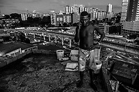SALVADOR, BRAZIL - FEBRUARY 13, 2014: Vanderlei Dias Costa, 31, stands on the roof of his home in a favela overlooking the Bonocô neighborhood as the abandoned metro system stretches off into the distance on February 13, 2014 in Salvador, Brazil. The metro system began construction over 13 years ago and has never operated. A new concessionary signed a contract for the maintenance and management of the metro last year and promises to have at least part of it functioning in 2014.<br /> <br /> Daniel Berehulak for The New York Times