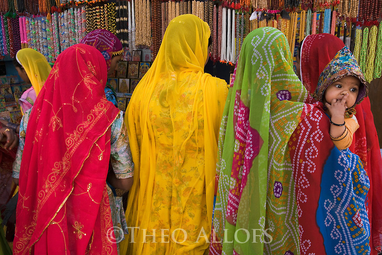 Rajasthani women in colorful dresses looking at jewelry in the Pushkar shopping street during the camel fair; .The annual Pushkar camel fair is one of the main tourist attractions in India, Pushkar, Rajasthan, India