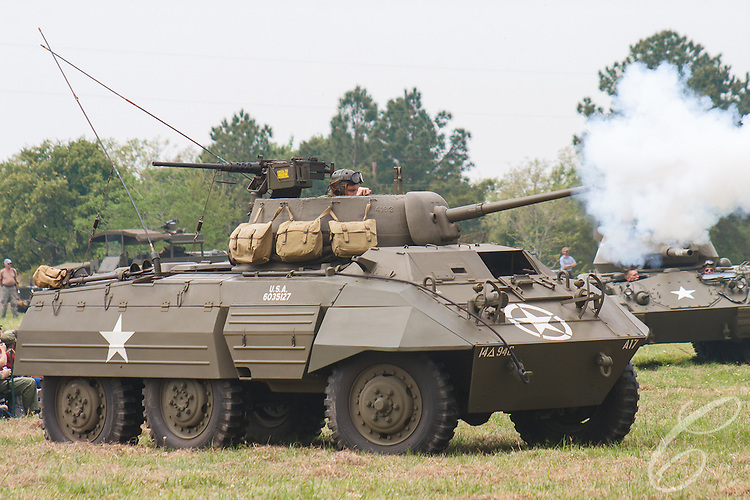"Reenactors showcase World War II tanks, half-tracks and support vehicles during the Museum of the America G.I.'s annual Open House on March 29, 2008 in College Station, Texas. An American M8 ""Greyhound"" armored car fires its 37mm gun for the assembled spectators."