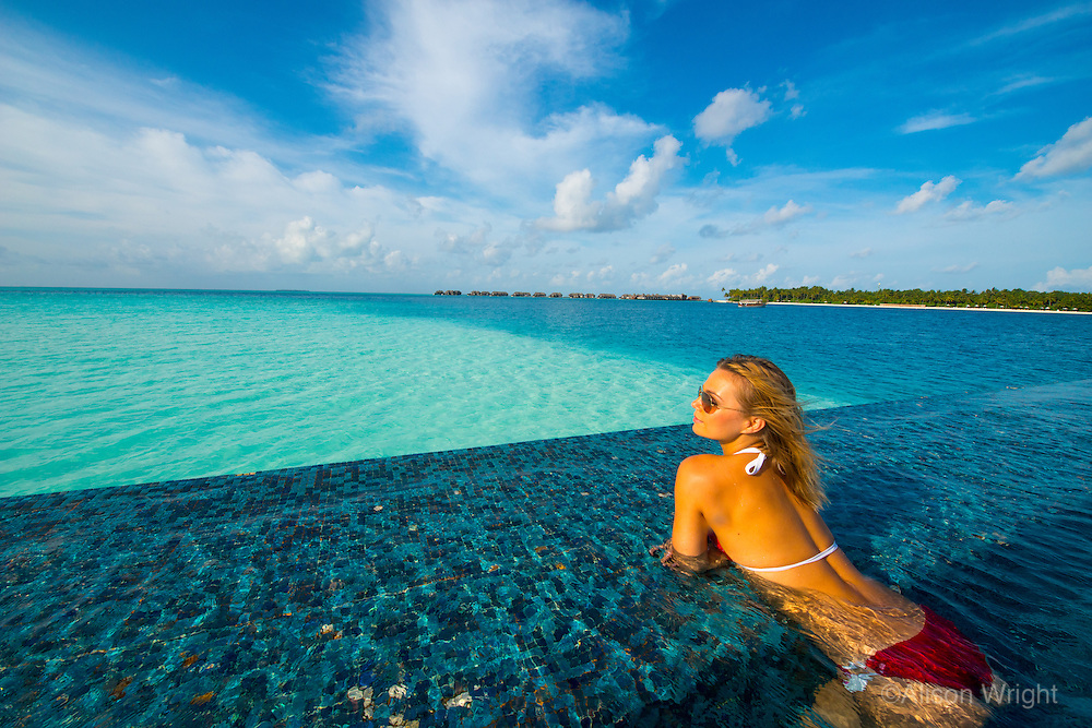 Maldives, Rangali Island. Conrad Hilton Resort. Woman in an infinity pool on the ocean. (MR)