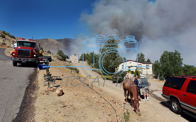 Firefighters battle a wind-driven fire that has destroyed at least two homes and a number of outbuildings in Topaz Ranch Estates, south of Gardnerville, Nev., on Tuesday, May 22, 2012. (AP Photo/Cathleen Allison)