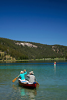 Canoers enjoy a pretty day on Wade Lake North of West Yellowstone Montana.