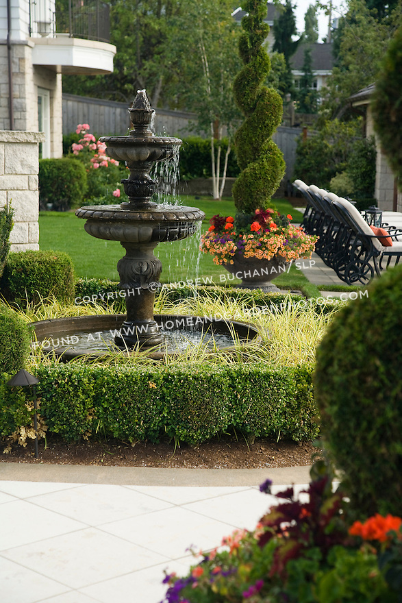Detail of a spilling fountain backed by a large pot filled with colorful summer annuals sitting on a poolside patio bordered by lawn and boxwood hedge.