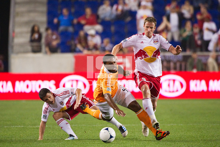Jermaine Taylor (4) of the Houston Dynamo gets tangled with Connor Lade (16) and Jan Gunnar Solli (8) of the New York Red Bulls. The New York Red Bulls defeated the Houston Dynamo 1-0 during a Major League Soccer (MLS) match at Red Bull Arena in Harrison, NJ, on May 09, 2012.