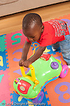 12 month old baby boy at home pushing plastic wheeled toy vertical