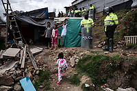 BOGOTA - COLOMBIA, 16-05-2020: Policías custodian el barrio Altos de La Estancia durante un censo hecho por la alcaldía local. Mas de 200 familias terminan el proceso de desalojo en el predio La Estancia al sur de Bogotá quedando sin ninguna ayuda ni un techo donde vivir durante la cuarentena total en el territorio colombiano causada por la pandemia  del Coronavirus, COVID-19. / Police guard the Altos de La Estancia neighborhood during a census carried out by the local mayor's office. More than 200 families are evicted from La Estancia farm at south of Bogota city and they left withoput any help and shelter to live during total quarantine in Colombian territory caused by the Coronavirus pandemic, COVID-19. Photo: VizzorImage / Mariano Vimos / Cont