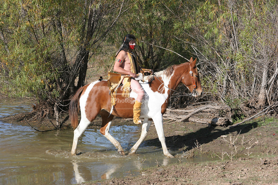 A Native American Indian man riding bareback on his horse in the water