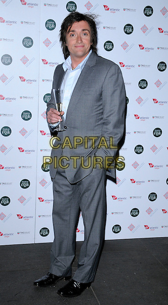 RICHARD HAMMOND.The Motor Sport Hall Of Fame event, the Roundhouse, London, England..February 10th, 2010.full length grey gray suit jacket trousers hand in pocket hamster champagne drink beverage .CAP/CAN.©Can Nguyen/Capital Pictures.