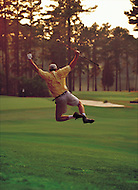 A golfer jumps for joy after making a shot