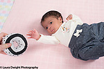 Newborn baby girl closeup on back pre-reaching toward high contrast black and white toy