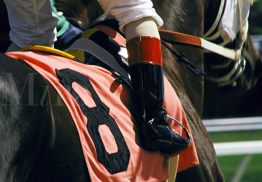 Jockey mounted on thoroughbred, close up shows boot in the stirrups, racing silks horses, equine, animals. #565.