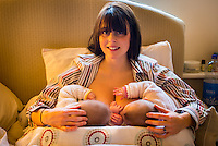 "A woman breastfeeding 5 month old twins at the same time on her bed in her bedroom.<br /> <br /> Image from the ""We Do It In Public"" documentary photography project collection: <br />  www.breastfeedinginpublic.co.uk<br /> <br /> Hampshire, England, UK<br /> 11/02/2013"