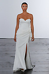 Model walks runway in a strapless sweetheart sheath bridal gown with draped skirt and slit, from the Dennis Basso for Kleinfeld 2018 Bridal Collection on October 5 2017, during New York Bridal Fashion Week.