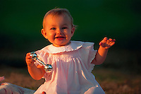 Baby girl smiling and shaking a silver rattle.