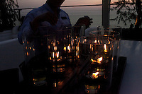 A staff lights evening candles in a bar on the roof top of a hotel on the Marine Drive, also known as The Queen's Necklace, Mumbai, India. Photo by Suzanne Lee