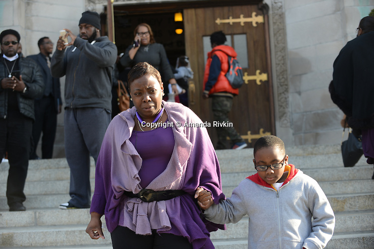 Mourners exit St. Sabina's during the visitation for Tyshawn Lee, 9, who was shot multiple times while playing basketball in an alley on November 2, 2015, in Chicago, Illinois on November 10, 2015. Police allege the killing was a retaliatory gang hit which would mark a new turn in Chicago's gang wars.