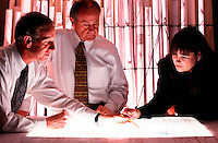 Three geologists, two men, one woman, looking at maps on light table.