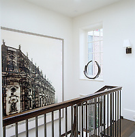 An architectural photograph dominates the wall at the top of the stairs