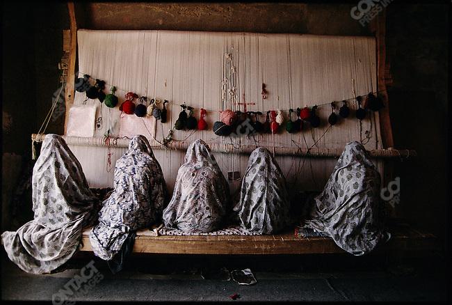 Women of the Mahbouban family weave a rug for export. Heris, Iran. September 1998