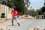 A Palestinian protester uses a slingshot to hurl stones towards Israeli security forces during clashes following a weekly demonstration against the expropriation of Palestinian land by Israel in the village of Kfar Qaddum, near Nablus, in the occupied West Bank on March 31, 2017. Photo by Mohammed Turabi