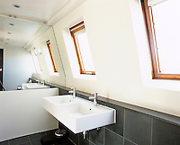A contemporary bathroom has been created in the attic