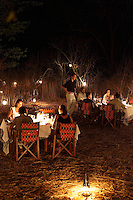 Guests enjoy an evening meal out in bush at the Singita Pamushana Lodge, Malilongwe Trust, Zimbabwe.