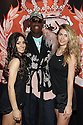 Players Candice left, Kristina right with coach Dennis Rodman center pose for a photo at the press conference for HQ's strippers basketball team in New York, on Thursday, Mar. 01, 2012. (AP Photo/ Donald Traill)
