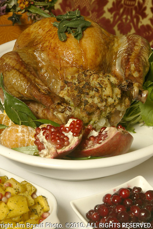11/12/04 turkey17 fea.Hunt Club Restaurant Chef Brian Scheehser's 15-pound turkey stuffed with sage and sausage stuffing.  On the left is baked winter squash with pomegranet seeds and ,right is cranberries tossed with sugar and cinnamon.  Jim Bryant Photo. ©2010. All Rights Reserved.