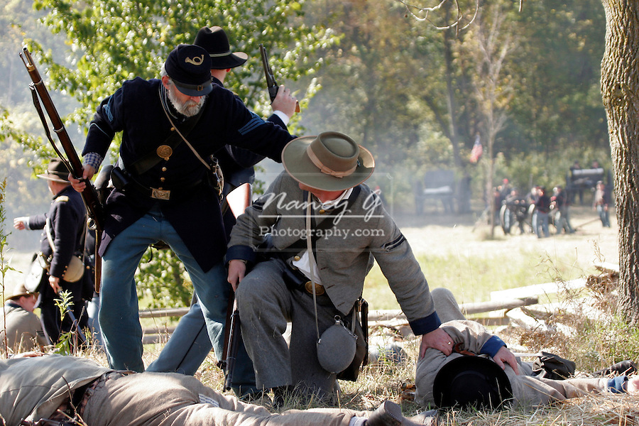 A Union and a Confederate soldier checking on the wounded soldier at a Civil War Reenactment