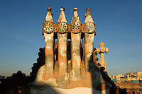 Detail of chimneys, Casa Batllo, 1875-77, renovated 1904-1906, Barcelona, Catalonia, Spain, pictured on January 9, 2007, at sunset. Casa Batllo, 43 Passeig de Gracia, was remodelled by Antoni Gaudi and Josep Maria Jujol for Josep Batllo, the owner of the house.  Inspired by the colours and shapes of marine life Gaudi produced an extraordinary building. Its local name is Casa dels ossos (House of Bones). It is decorated with a mosaic made from broken ceramic tiles (trencadis) in shades ranging from orange to greenish blues. The roof may be an allegory of the story of St George (patron saint of Catalonia) and the Dragon, its arch representing the dragon's back. Picture by Manuel Cohen.