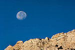 Moon setting over jagged rocky mountain ridge in the Cathedral Range; Yosemite National Park; California