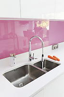 The successfully redesigned kitchen/dining area is reflected in the pink splashback that runs the length of one wall