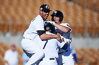 Glendale Desert Dogs catcher Kyle Farmer (7) is mobbed by teammates Nicky Delmonico (23) and A.J. Reed (14) after a game winning walk off hit during an Arizona Fall League game against the Mesa Solar Sox on October 13, 2015 at Camelback Ranch in Glendale, Arizona.  Glendale defeated Mesa 8-7.  (Mike Janes/Four Seam Images)