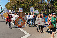 """Mohammed holds the """"Occupy Orange County"""" sign as Occupy Orange County, Irvine marchers cross the intersection of Alton and Paseo Westpark in Irvine, CA as a part of their Saturday protest against banks.  Many signs are visible."""