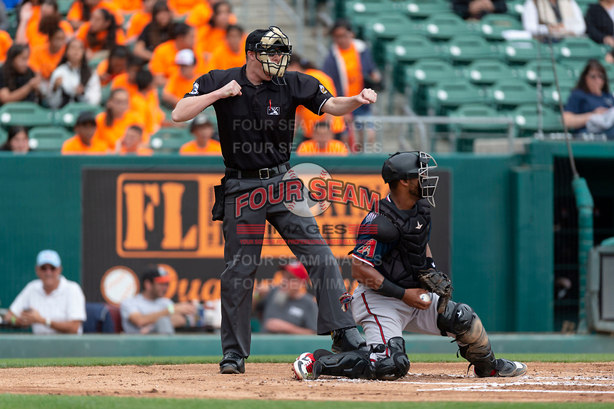 Home plate umpire Clint Vondrak calls strike three on a batter behind catcher Alberto Rosario (6) during a game between the Reno Aces and the Fresno Grizzlies at Chukchansi Park on April 8, 2019 in Fresno, California. Fresno defeated Reno 7-6. (Zachary Lucy/Four Seam Images)
