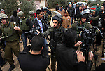 A member of the Israeli military puts his hand on the lens of cameras as he tries to prevent coverage, as others investigate the attack on the Hamayel home, that was burnt by suspected Jewish extremists using petrol bombs, in the village of Abu Falah, northeast of Ramallah, on November 23, 2014. Suspected Jewish extremists firebombed a house in a Palestinian village in the occupied West Bank early, its mayor told AFP, pointing the finger of blame at local settlers. Masud Abu Mura, mayor of Khirbet Abu Falah, said four women were inside the house at the time, but they all escaped unharmed. Photo by Shadi Hatem