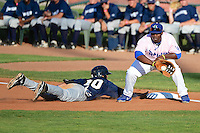 Angel Ortega (10) of the Helena Brewers slides back to first base as Justin Chigbogu (56) of the Ogden Raptors grabs the throw at Lindquist Field in Ogden Utah on July 20, 2013.  (Stephen Smith/Four Seam Images)
