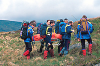 Mountain rescue team rescuing a climber that has fallen down onto rocks. They are carrying him on a specially designed stretcher used for recovering casualties from remote places...© SHOUT. THIS PICTURE MUST ONLY BE USED TO ILLUSTRATE THE EMERGENCY SERVICES IN A POSITIVE MANNER. CONTACT JOHN CALLAN. Exact date unknown.john@shoutpictures.com.www.shoutpictures.com.