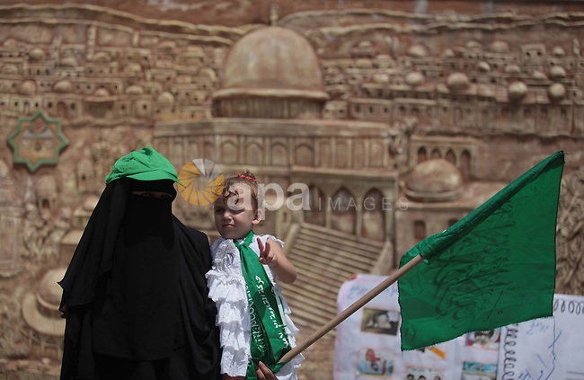A Palestinian woman holds her daughter as their take part in a protest to support the Palestinian parliament, Aziz Dweik, in front of the Legislative Council in Gaza City on June 19, 2014. Israeli forces raided Hebron and detained speaker of the Palestinian parliament, Aziz Dweik, along with five other parliamentarians during in an operation to locate three Israeli teens in the West Bank. Photo by Ashraf Amra