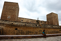 Bari: This is a photo of me, made by a friend of mines, while sitting on the edge of the external wall that surrounds the moat of the Normanno-Svevo (Swabian) castle, near the town historical center, under a cloudy sky. A side of the castle itself, with two of its characteristic towers, is on the background. In fact, my colorful clothes appear to enhance the beautiful seriousness of the ancient building. This is a slight enlargement of a part of the original photo.<br /> <br /> You can download this file for (E&amp;PU) only, but you can find in the collection the same one available instead for (Adv).