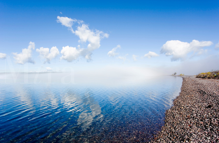 Early morning fog clearing off of Yellowstone Lake, with clouds and intense blue sky reflected in water surface, shoreline leading into distance, Yellowstone National Park, WY