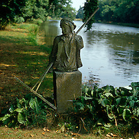 A stone sculpture holding a wooden rake on the bank of a river
