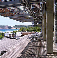 A rolling teak deck that faces the ocean runs along the outside of the living area which has hydraulic shutters to shield it from the wind and the sun